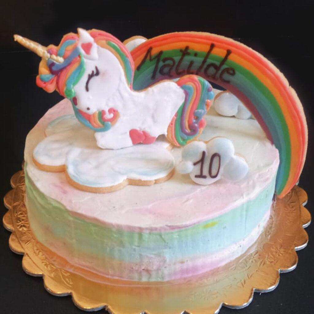 torta con crema e fragole e un bellissimo UNICORNO + arcobaleno in frolla decorati in ghiaccia reale. Copertura panna e mascarpone colorato