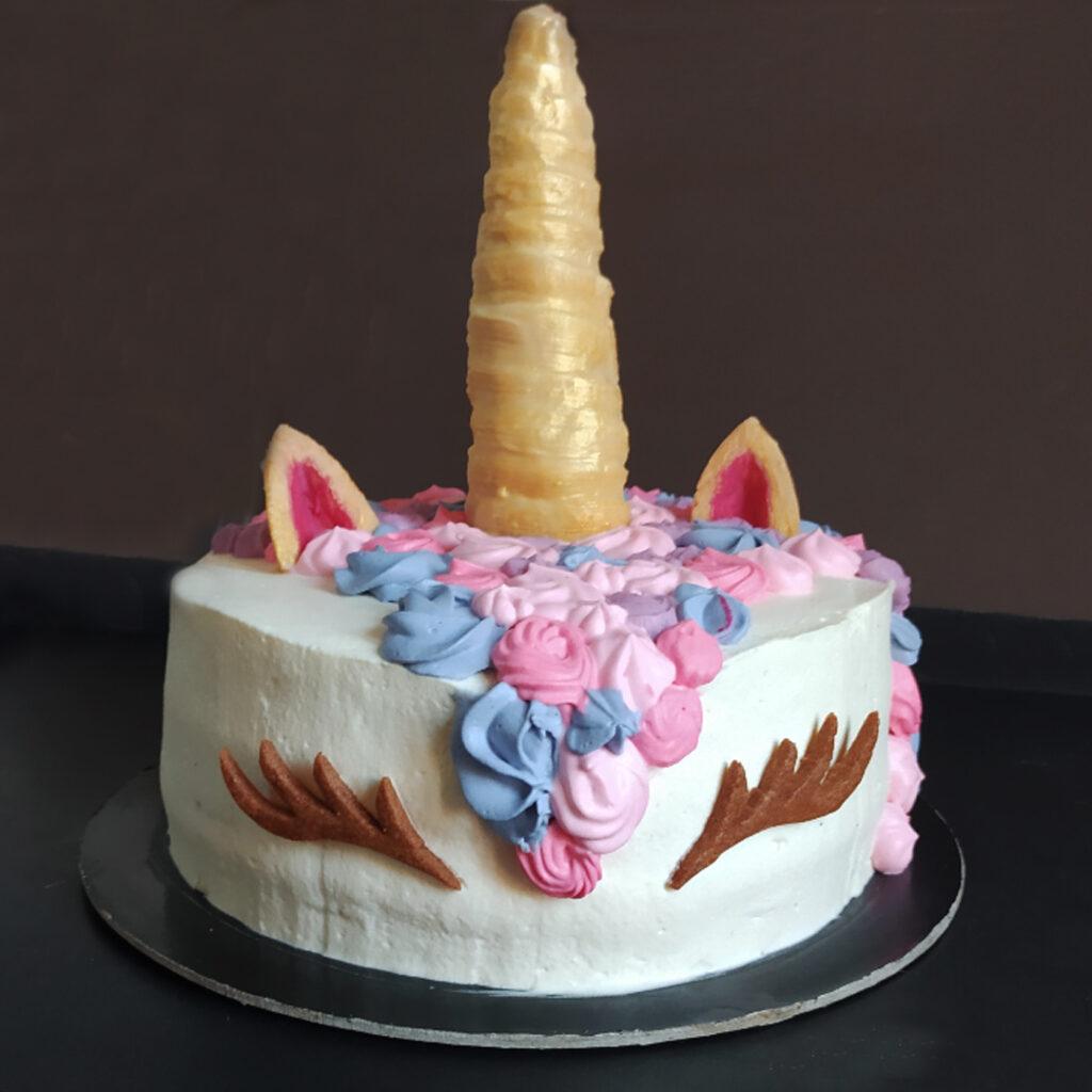torta chantilly con corno, orecchie e occhietti in biscotto e panna in diverse tonalità di rosa e lilla in superficie